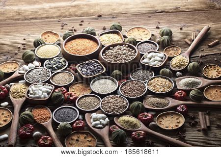 Set of different leguminous vegetables in bowls on wooden table