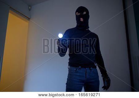 Burglar Wearing A Balaclava Holding A Flashlight