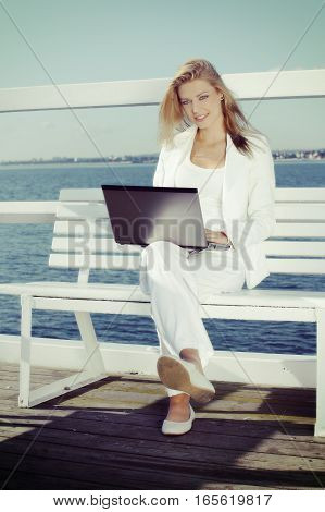 Work At Leisure Time. Young Blonde Woman With Laptop On The Pier