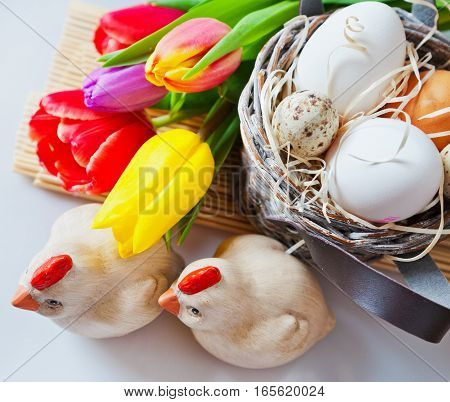 Traditional Czech easter decoration - white eggs with tulip flowers in the basket nest quail eggs and wooden chickens. Spring easter holiday arrangement.