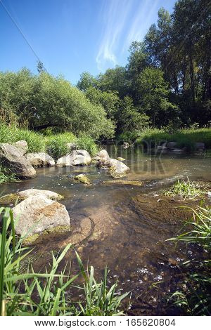 Landscape with clear water in fast small river quickly runs between stones in summer day. Vertical photo