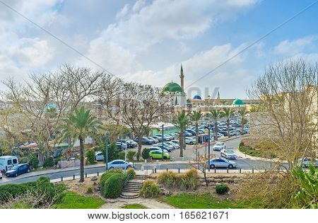 ACRE ISRAEL - FEBRUARY 20 2016: The green domed Al-Jazzar mosque is seen through the greenery of Hafir garden on February 20 in Acre.