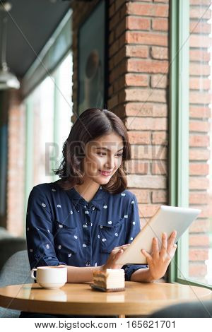 Beautiful cute asian young businesswoman in the cafe using digital tablet and drinking coffee smiling