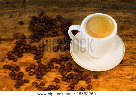 cup of coffee and coffee beans on wooden vintage table