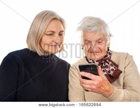 Picture of two elderly women typing on a smartphone