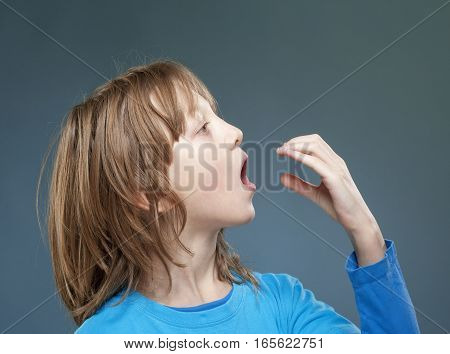 Boy Pretending to be Eating Something Invisible.