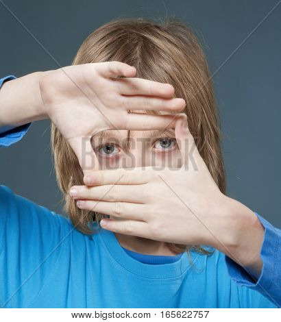 lBoy with Long Blond Hair Looking Through a Finger Frame