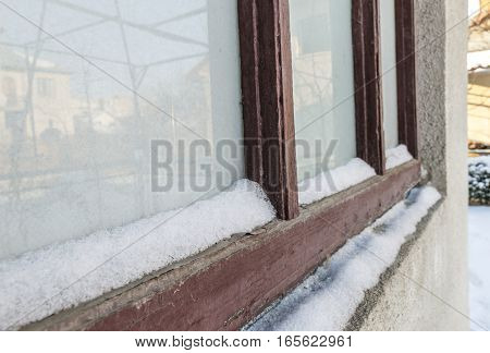 A view of brown old snow covered window.