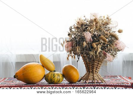 Beautiful autumn composition of Basket with healing herbs dried grass and flowers for use in alternative medicine spa herbal cosmetics herbal medicine preparing infusions decoctions tinctures powders ointments butter tea bath. Autumn pumpkins with flowers