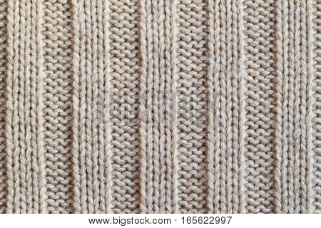 Creamy wool knitted warm clothes for the winter fabric texture background