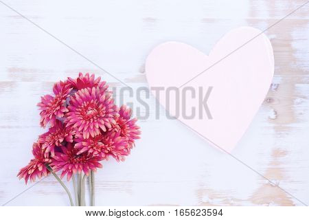 bunch of beautiful red flowers on a white vintage wooden background with wooden heart