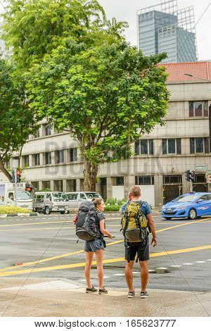 SINGAPORE - OCTOBER 07 2016: Two backpackers standing at a road crossing in central Singapore when raining.
