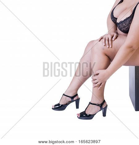 Plus size model in black high heels shoes xxl woman isolated on white studio background legs fatigue