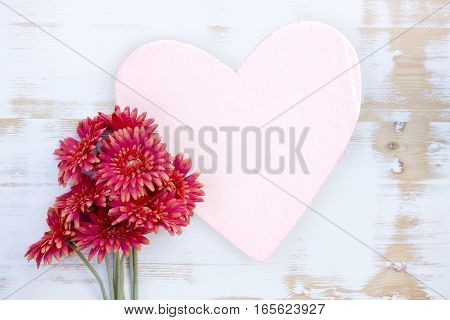 red flowers on wooden white table with heart