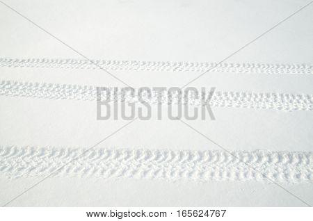 Tire tracks in fresh snow in winter in sunny day