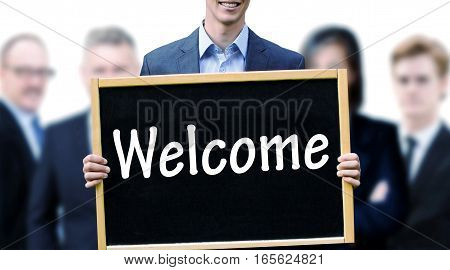 young businessman with group of businesspeople and holding up a chalkboard with the word Welcome