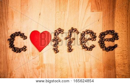 Coffee beans on wood background. Shape of word Coffee made from coffee beans, decorated with red heart on wooden surface. Roasted coffee beans on rustic wood background. Top view. .