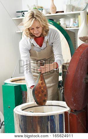 Mature Woman In Pottery Studio Firing Vase In Kiln
