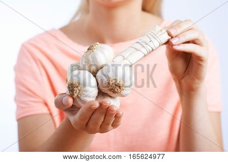 Close Up Of Woman Holding Garlic In Studio