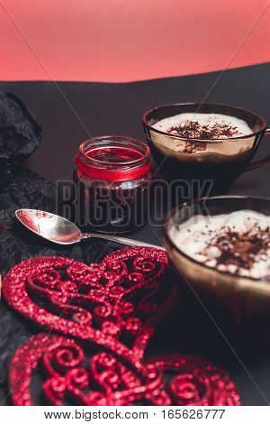 Two Cups Of Coffee, Cappuccino Near Red Hearts On Black Table Background. Valentine Day. Love. Roman