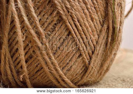 Close up of hank of twine reel of rope ball of hemp thread on jute background