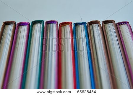 row of multicolored hardcover Closed  book on a light background