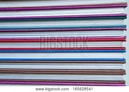 Closed book and book in multicolored hardcover on a wooden table