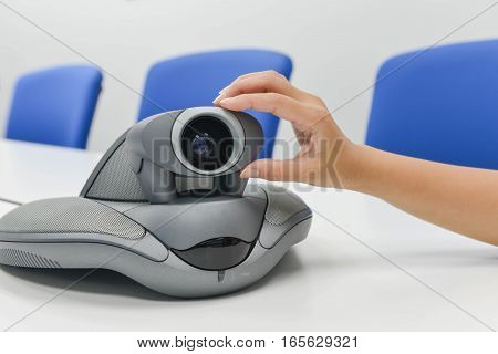 Human hand is adjusting thecamera of VDO IP conference device