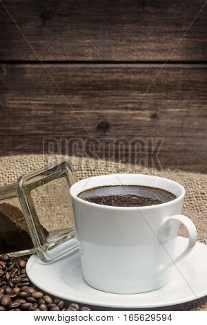 Vintage photo of the white cup of coffee standing on the sackcloth. Around it are scattered coffee beans and ground coffee glass Wooden desk on the background fills a half of the photo. Vertically.