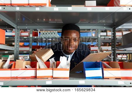 Young Factory Worker With Clipboard In Warehouse