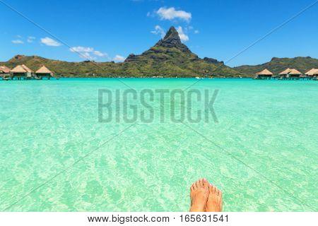 Female crossed legs over tropical blue lagoon and Otemanu mount Bora Bora near Tahiti in French Polynesia.