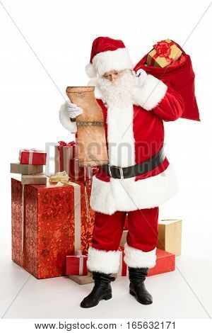 Happy Santa Claus standing with a pile of Christmas gifts and a big sack on back reading wishlist