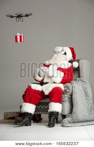 Santa Claus sitting on grey armchair wearing virtual reality headset using hexacopter drone