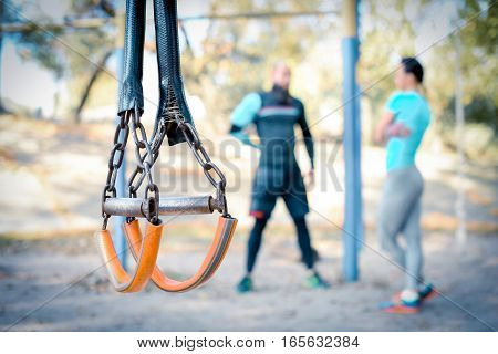 Sportive couple working out together in the park with sport equipment on foreground