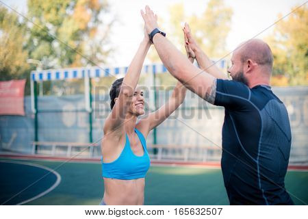 Friends giving high five after training on the stadium