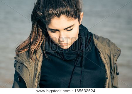 Outdoor portrait of a thoughtful teenage girl wearing khaki parka. Toned effect