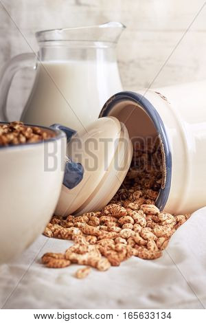 Puffed barley cereal spilling from jar with pitcher of milk in background