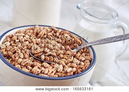 Puffed barley cereal in bowl with pitcher of milk in background