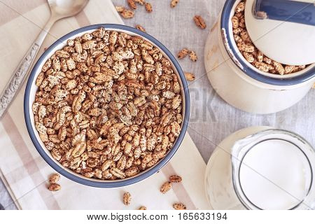 Puffed barley cereal in bowl with pitcher of milk. Top view