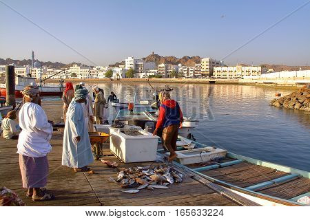 MUSCAT, OMAN - FEBRUARY 11, 2012: Fishermen at The Muttrah Fish docks early morning with Muttrah corniche in the Background