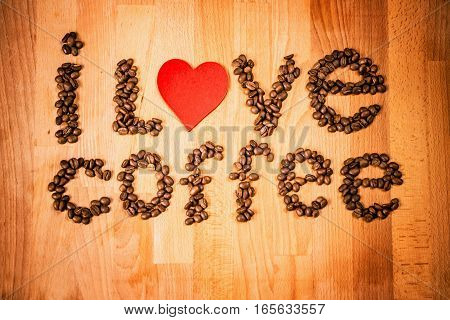 Coffee beans on wood background. Shape of words I Love Coffee made from coffee beans, decorated with red heart on wooden surface. Roasted coffee beans on rustic wood background. Top view.