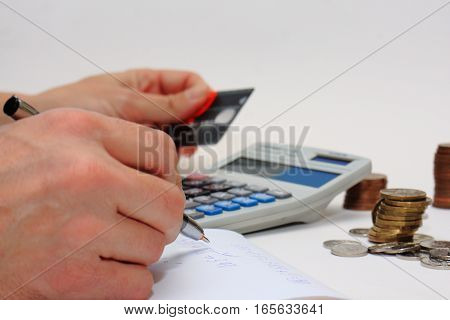 Counting money using calculator credit card pen paper and coins hands