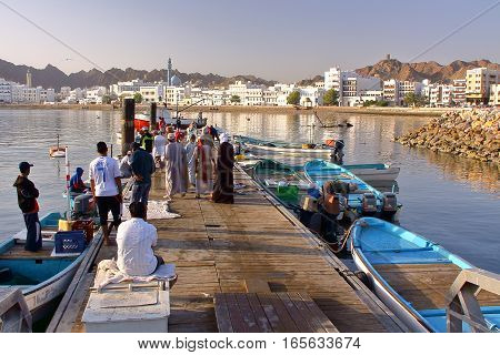 MUSCAT, OMAN - FEBRUARY 11, 2012: Fisherman at The Muttrah Fish docks early morning with Muttrah corniche in the Background