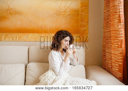 Pretty curly hair girl in a white silk dressing gown in the early morning drinking coffee