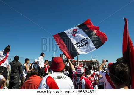 Buenos Aires Argentina - October 6 2013: River Plate supporters sing and dance while waiting for the stadium doors to open to attend a soccer game at the Estadio Monumental Antonio Vespucio Liberti in the city of Buenos Aires Argentina
