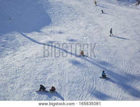 people sledding in the winter in the mountains