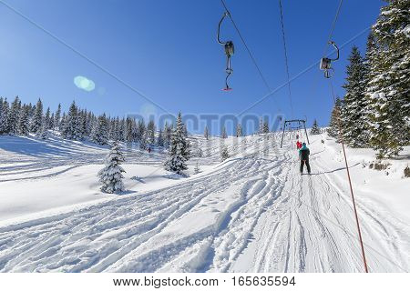 Skiers On Ski Lift, On A Lovely Sunny Day In The Carpathian Mountains