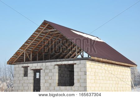 Roofing Construction. Building new house from autoclaved aerated concrete blocks vs bricks with unfinished roofing metal tiles construction.