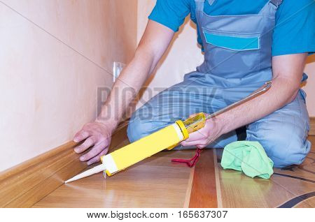Repairman Installing Skirting Board Oak Wooden Floor with Caulking Gun Silicone from Cartridge. Flooring with Wooden Batten Repair.