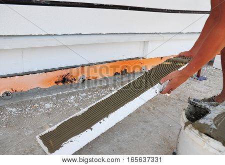Man's Hand Plastering a Wall Styrofoam or Foam Board Insulation. Styrofoam Insulation for Basement Walls. House Insulation.